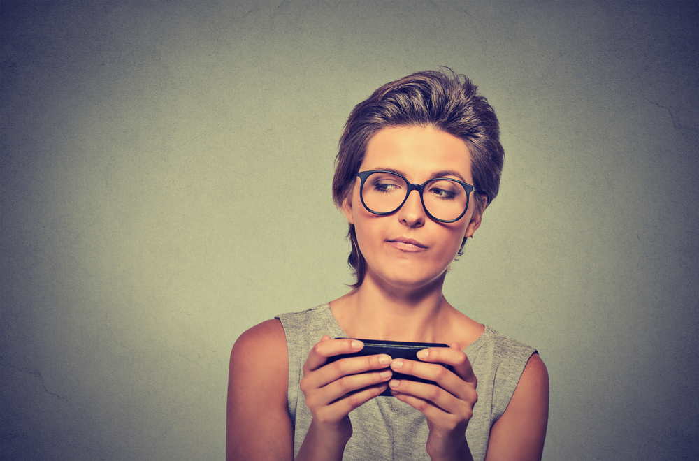 Portrait young angry woman with glasses unhappy, annoyed by something on cell phone while texting receiving bad sms text message isolated grey wall background. Human face expression emotion reaction